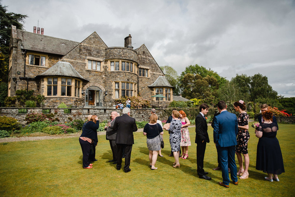 wedding party talking on lawn of cragwood house hotel