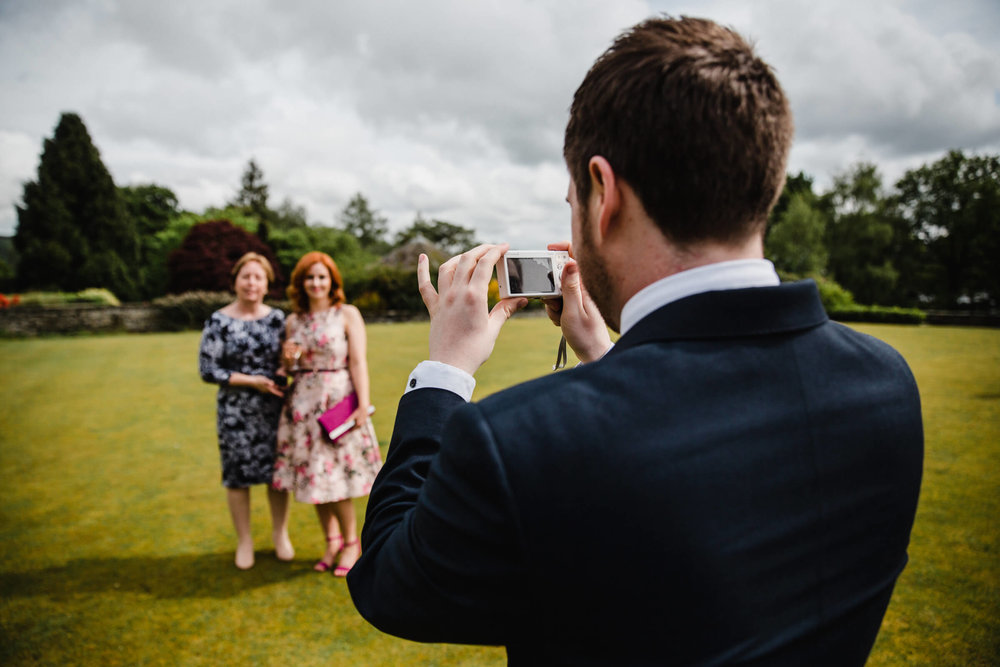 wedding guests having photograph taken on the lawn