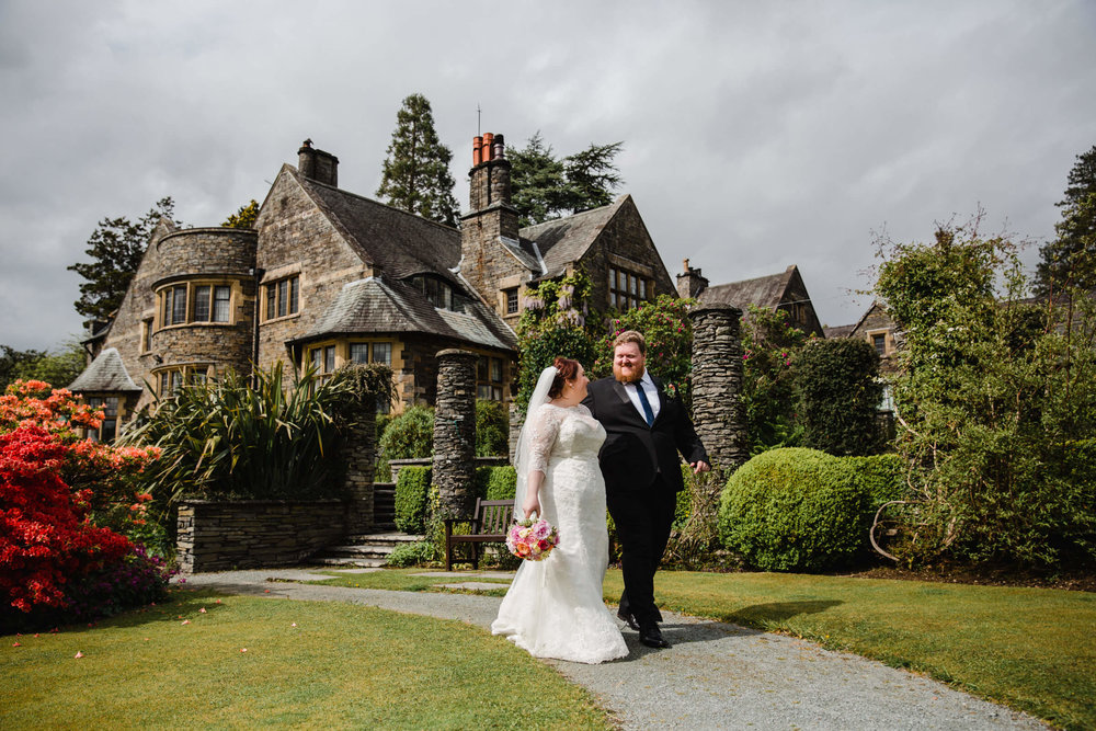 bride and groom portrait walking down path with cragwood country house hotel in the background