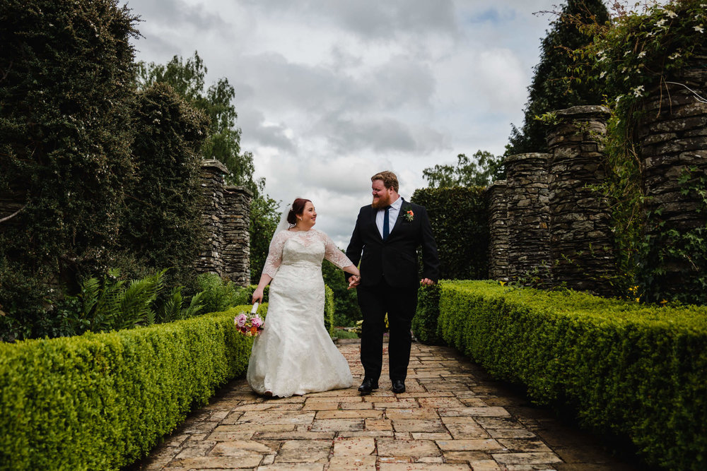 bride and groom holding hands whilst walking in the gardens of the house
