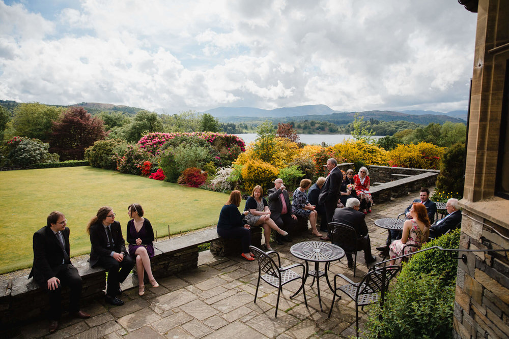 wide angle photograph of wedding party on terrace with cumbrian hills in the backdrop and lake windermere