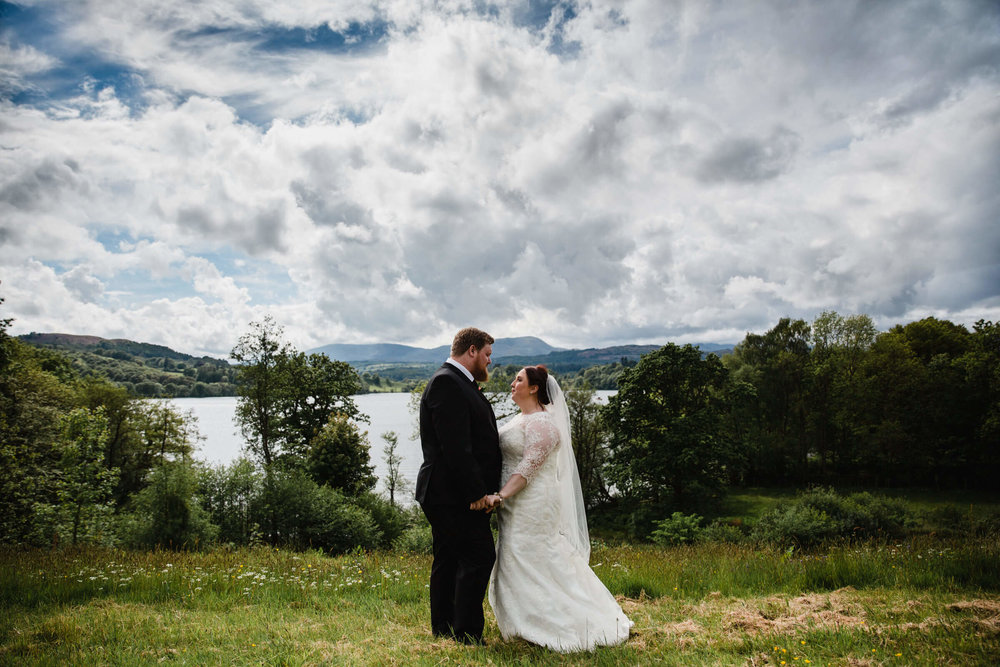 bride and groom with lake windermere backdrop and a sky of white clouds