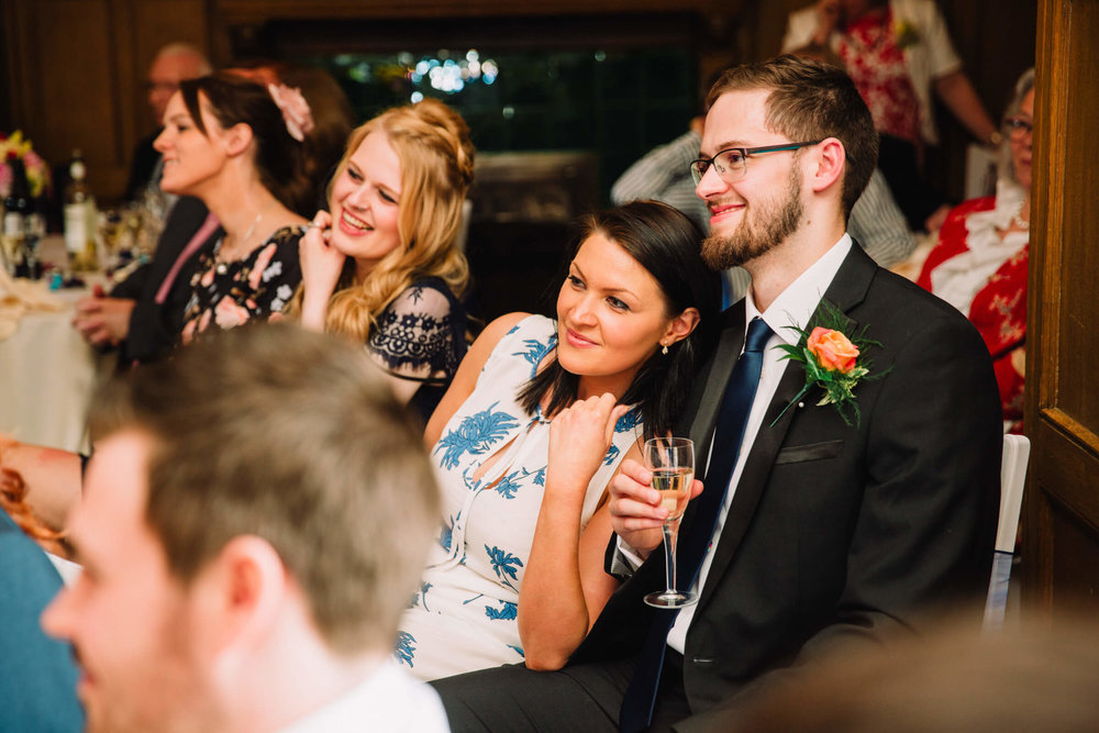 guests looking on at wedding speeches with big smiles