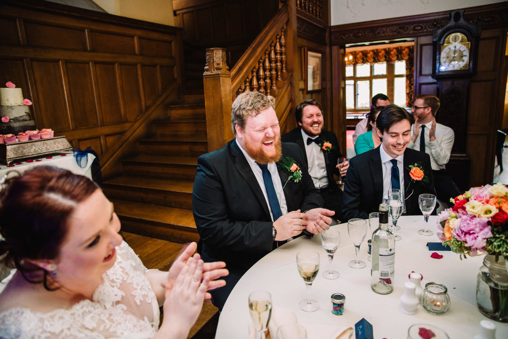 groom and wedding party laughing at speeches