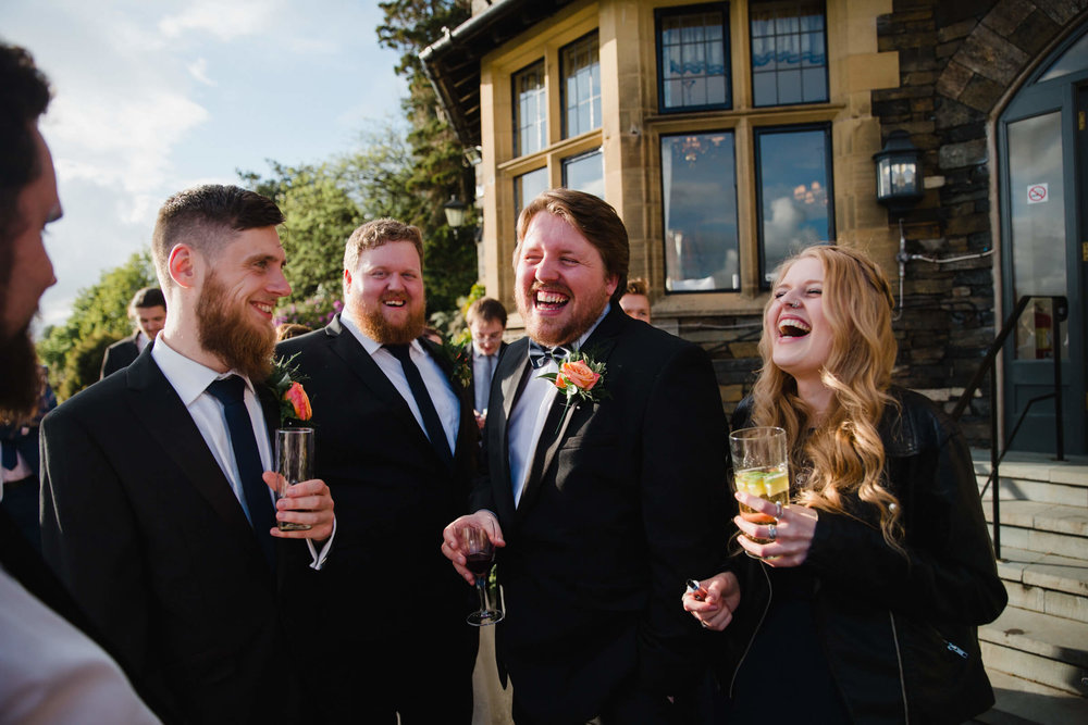 groomsmen laughing out loud in the garden