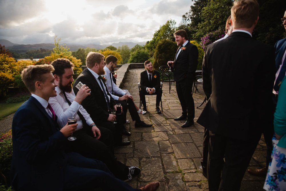 groomsmen laughing on terrace in garden