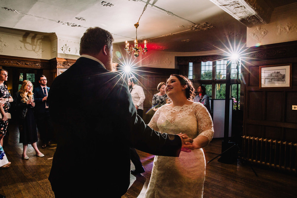 first dance of newlyweds surrounded by family on dancefloor