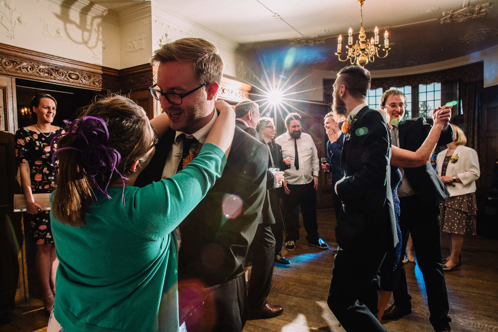 wide angle photograph of wedding party all dancing on the dance floor