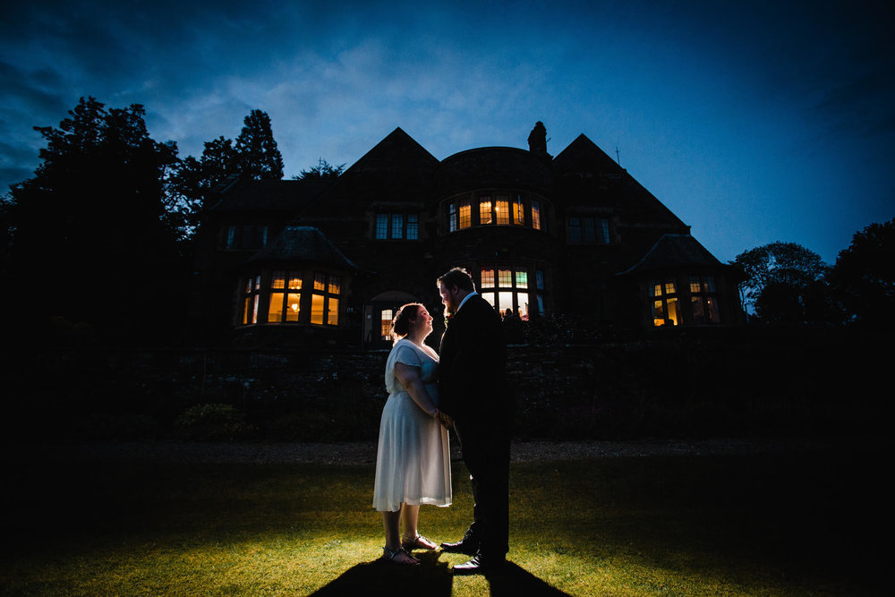 night time portrait of bride and groom with cragwood country house hotel in the background lit up