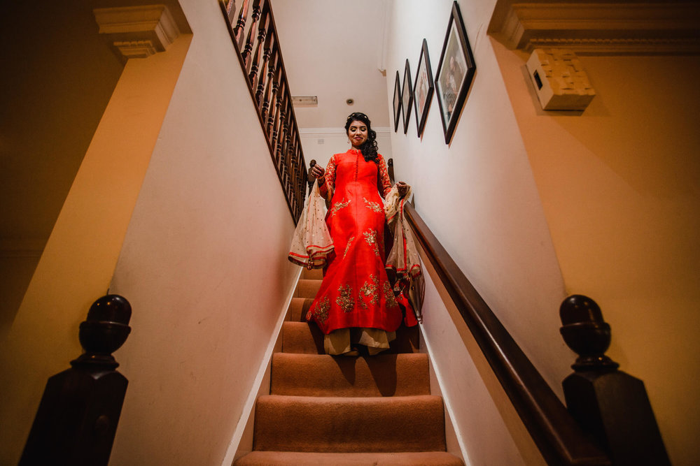 bride making her way down the stairs in red dress