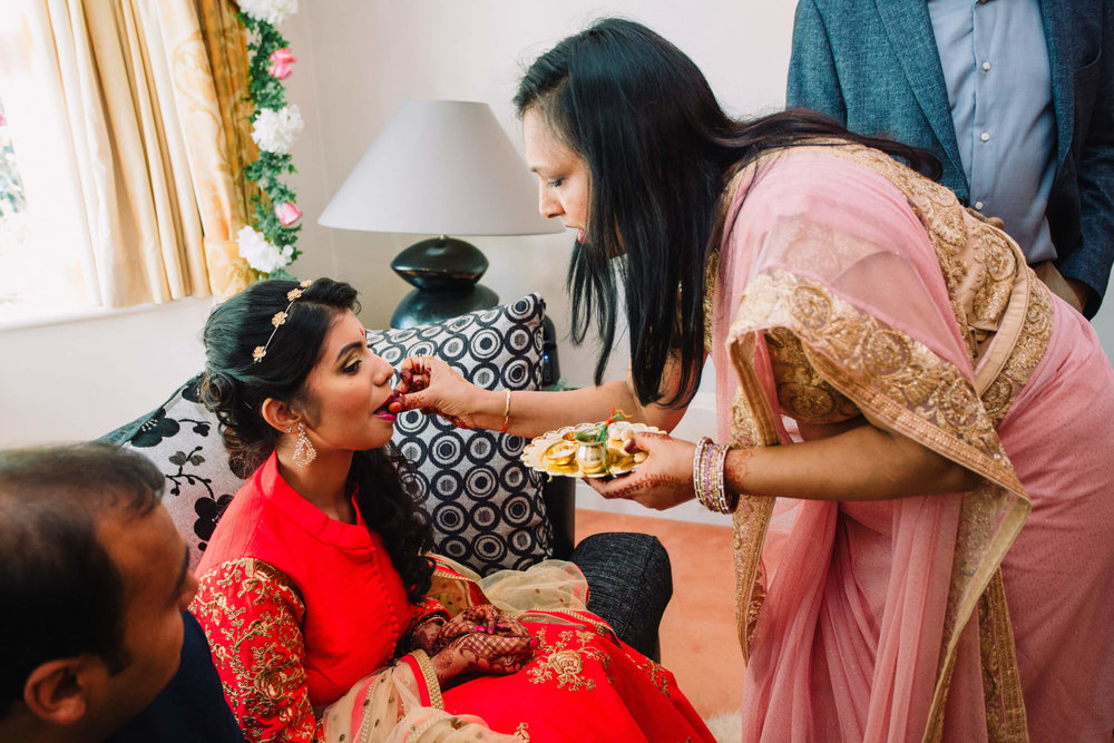 bride being fed a treat by wedding guest