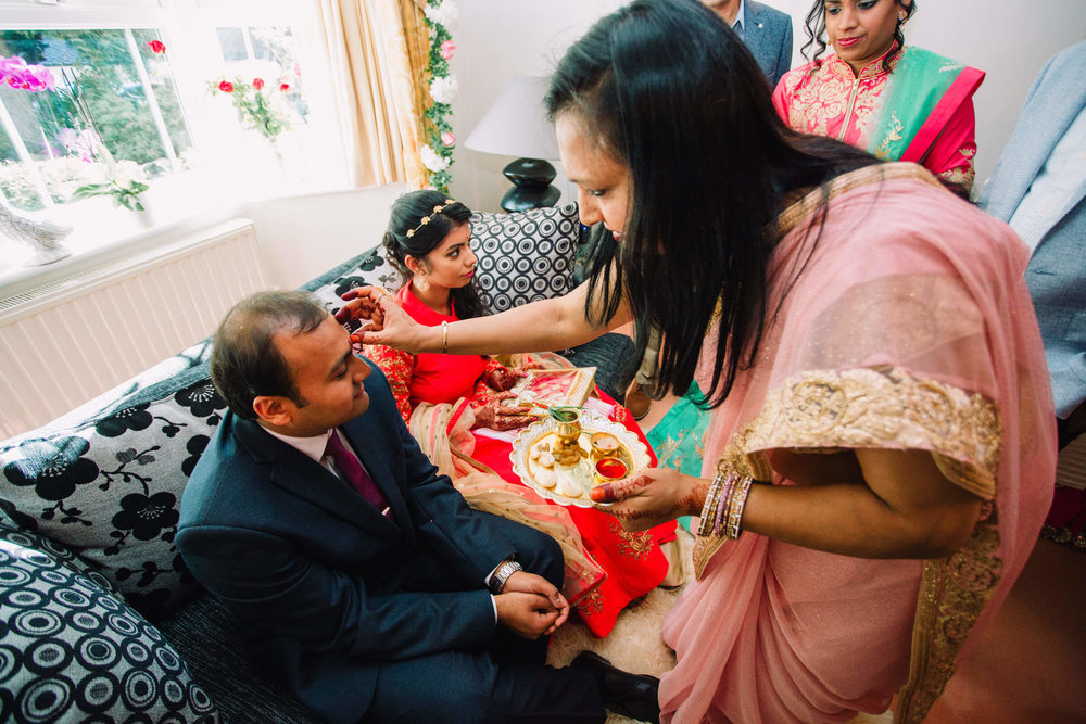 groom receiving bindi from bridesmaid