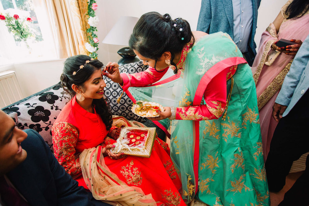 bride receiving bindi from wedding guest