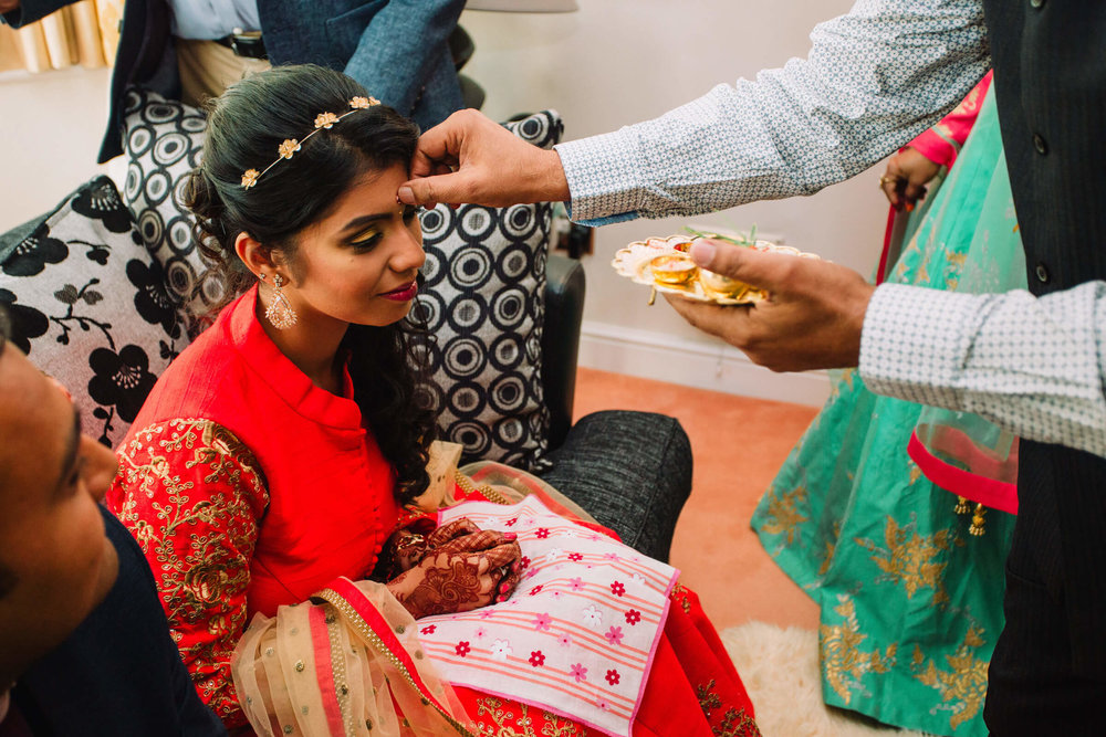 bride receiving red bindi on forehead