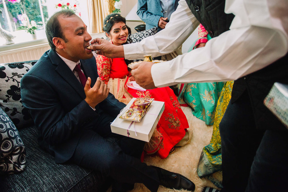 groom being fed food from wedding guests