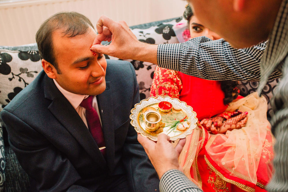 groom receiving the red bindi on to his forehead