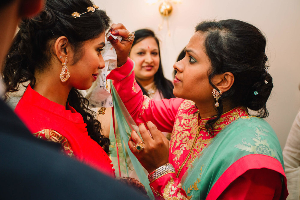 intimate moment of bride and bridesmaid sharing bindi with family