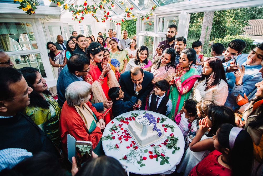 family sharing the cake between guests