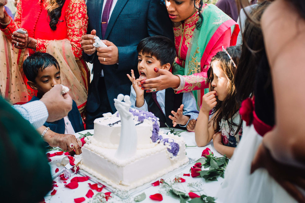 pageboy licks his fingers with wedding cake