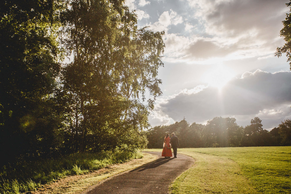 sunset portrait of bride and groom walking on path away from camera with the sun setting in background