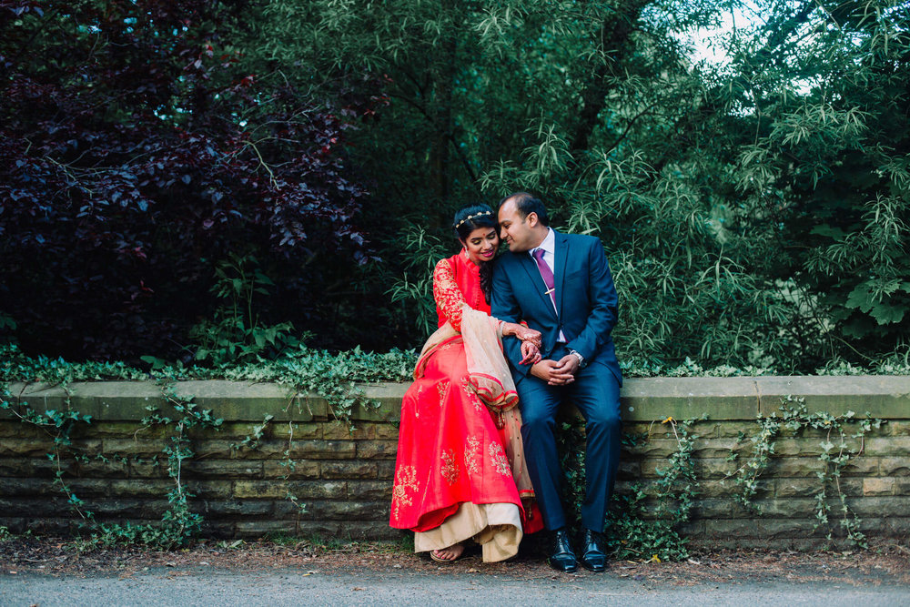 wedding couple sat on wall for portrait sharing an intimate moment together