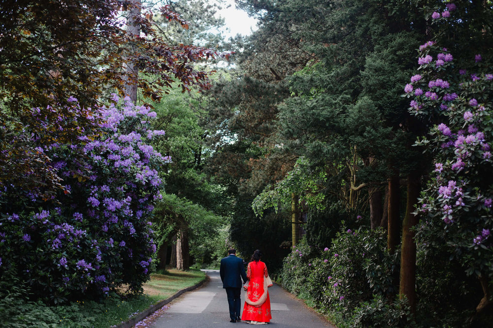 wide angle photograph of bride and groom walking down path at oddfellows on the park