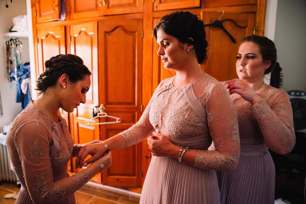bridesmaids fastening bracelet onto wrist