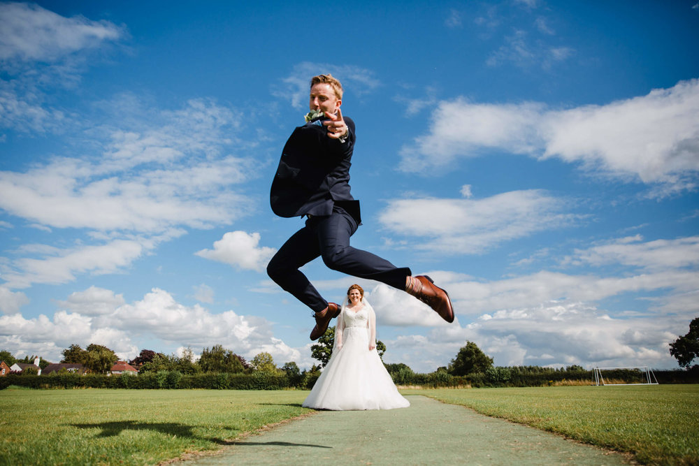 Groom Jumping over Bride in Playing Field