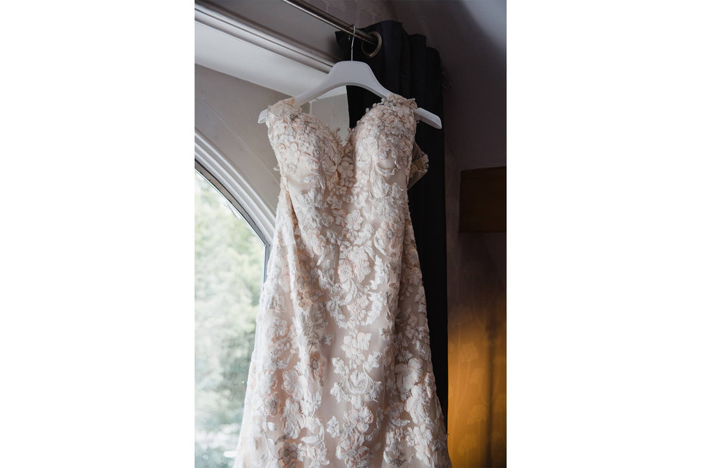 Portrait photograph of Justin Alexander dress hung up on curtain rail of bridal suite
