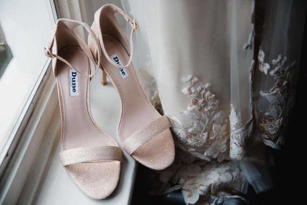 A Pair of pink Dune Wedding Shoes sit on the window sill next to the brides wedding dress