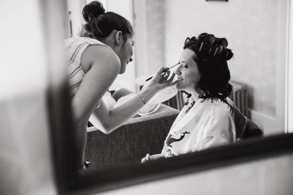 black and white photograph of bride in the mirror having make up preparation done before wedding