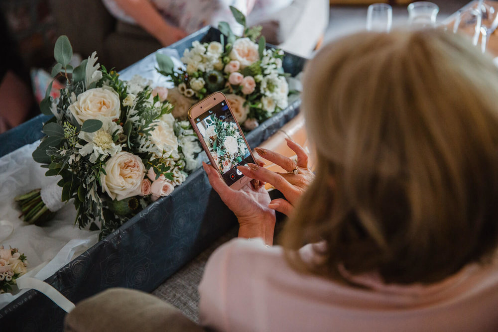 Mother of the bride taking photographs of wedding bouquets using camera phone