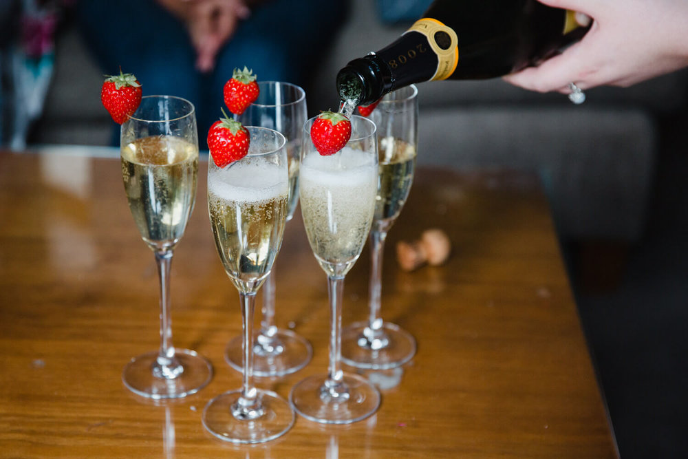Close up photograph of champagne being poured into flutes with strawberries
