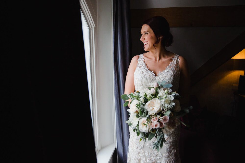 bride portrait holding bouquet in the window of eleven didsbury park hotel