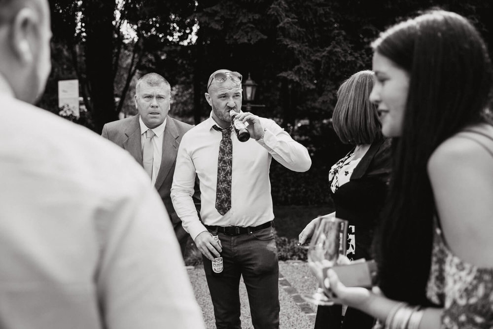 Black and White photograph of wedding guests having drinks