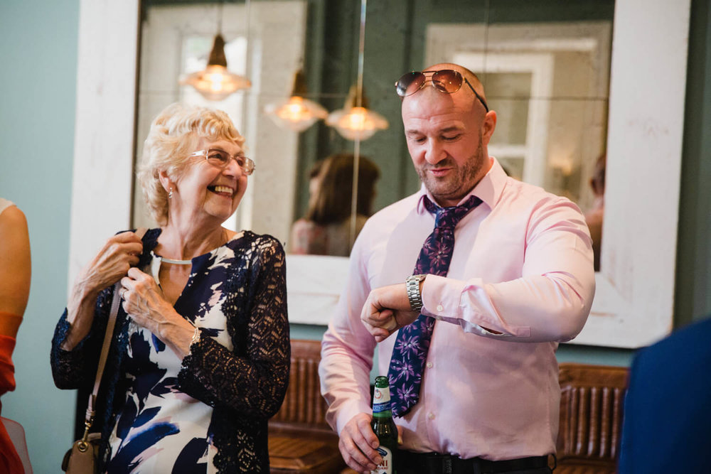 Groom sharing a joke with aunty while he looks at his watch