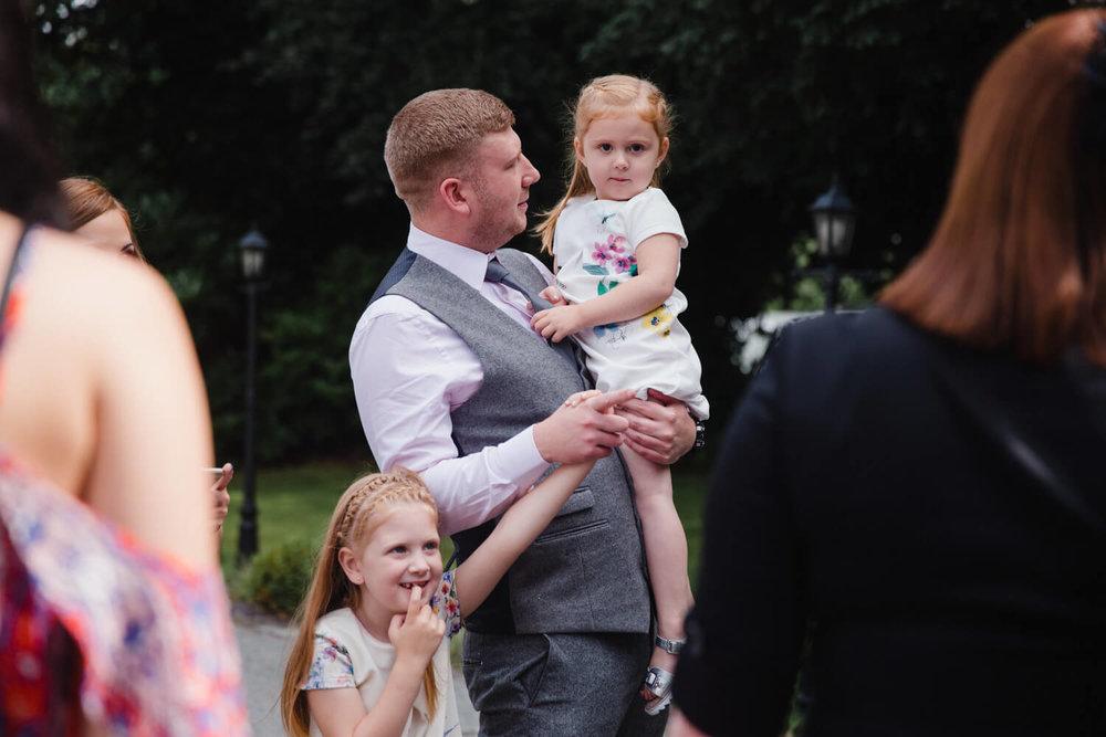 usher holding flower girl in the carpark