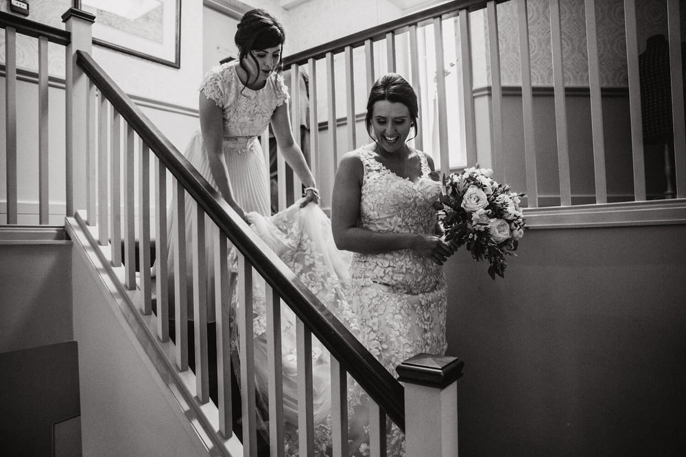 bridesmaid holding brides dress while she walks down the stairs to wedding ceremony