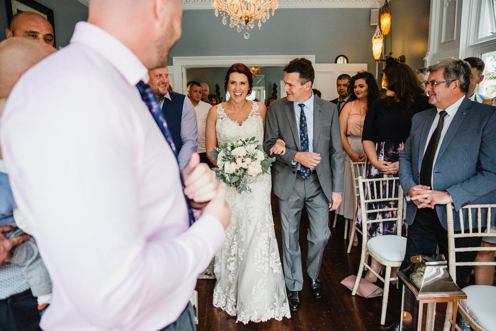 bride linking arms with father and smiling at groom down the aisle of wedding ceremony