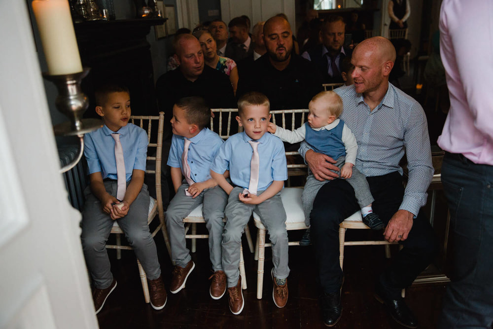 pageboys and ushers sat at the top of the aisle during wedding ceremony. Baby poking pageboy in the ear.