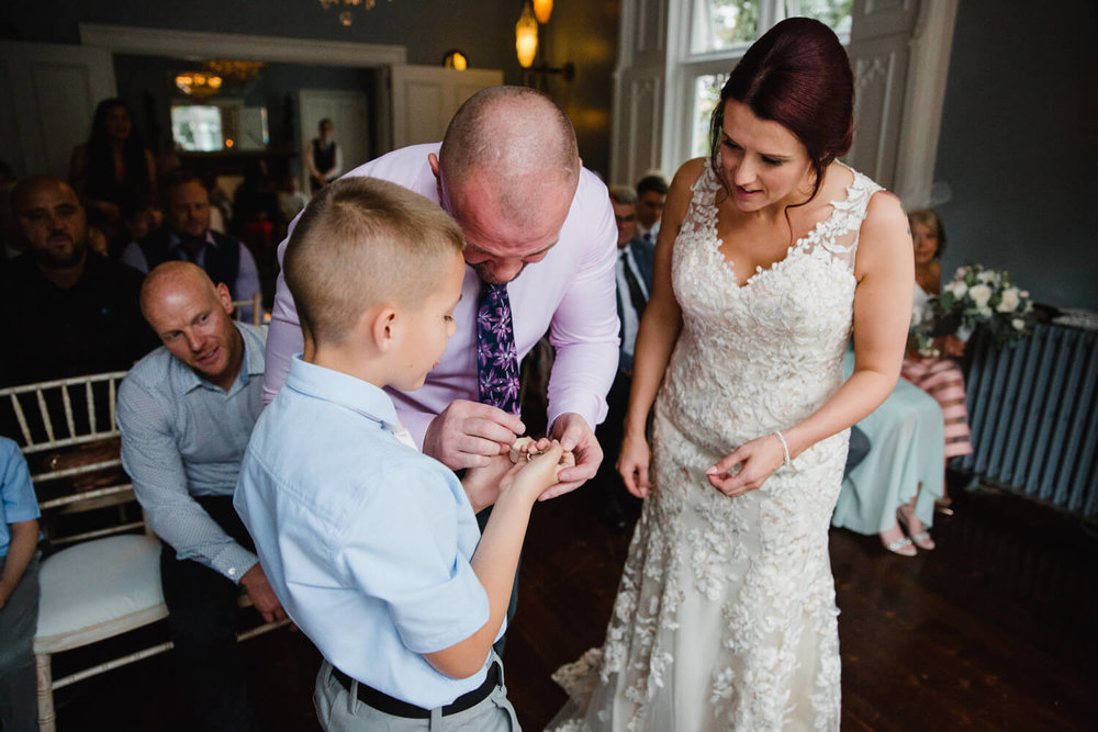pageboy presents wedding rings to couple