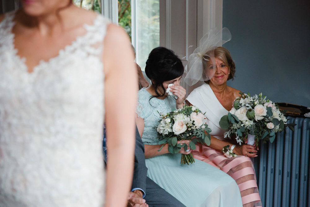 bridesmaid wiping away a tear with a tissue