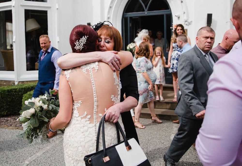Aunt congratulating bride with hug outside of wedding venue