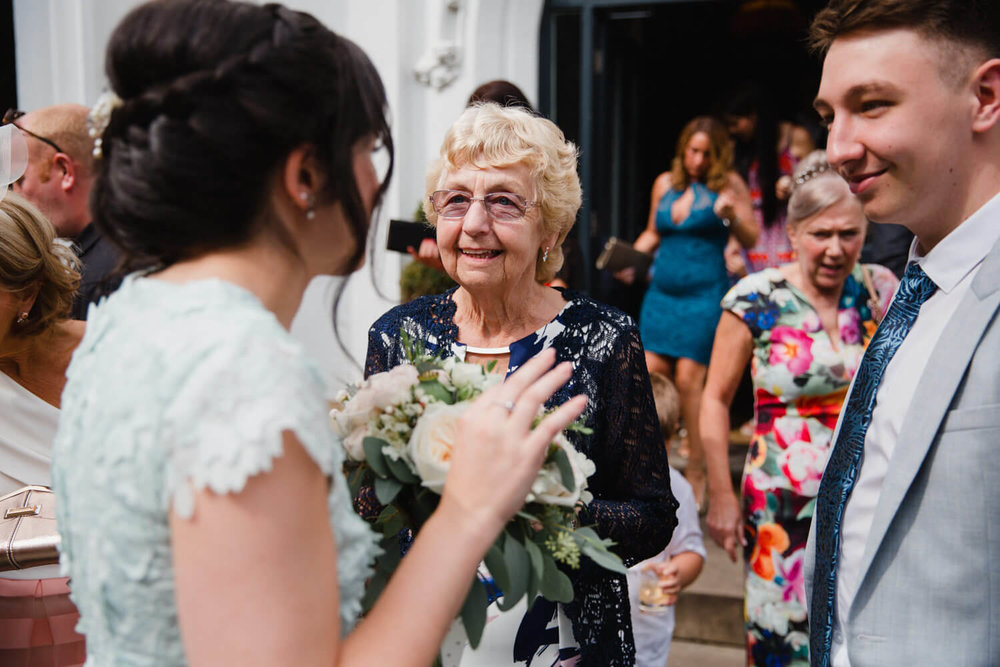 Grandma chatting to bridesmaid after wedding ceremony