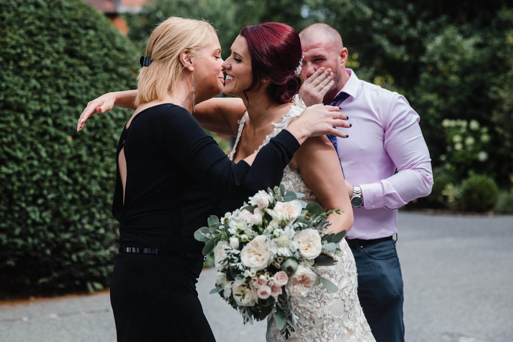 bride being congratulated by family guest after the wedding service
