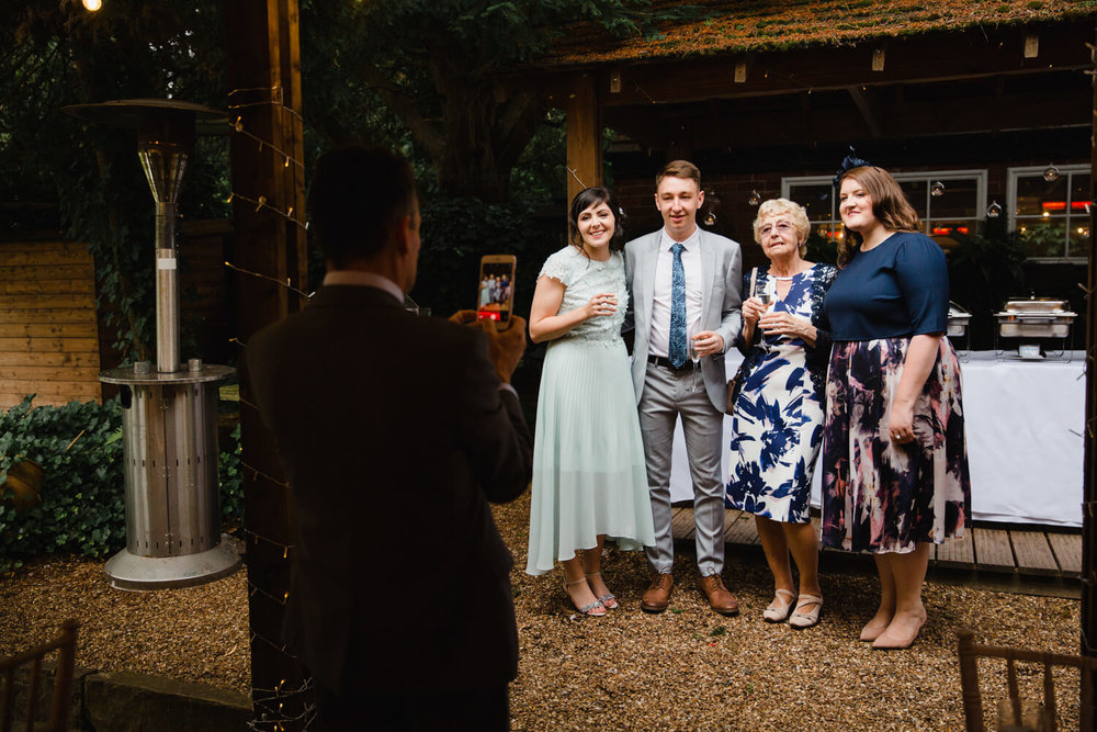 wedding guests being photographed by father of bride with a camera phone