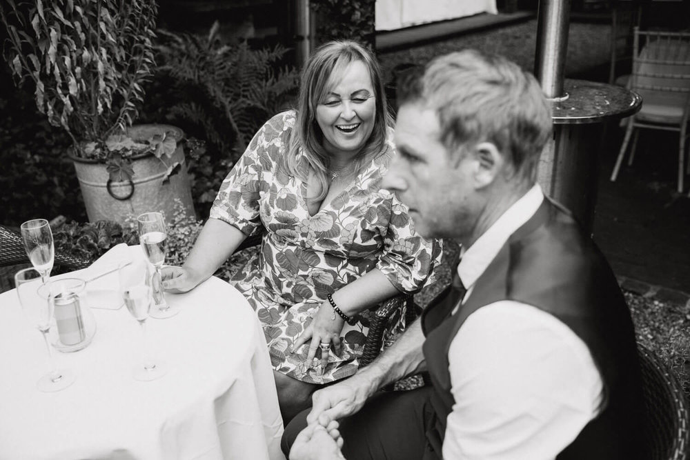 black and white photograph of wedding guests sat at table laughing and joking together