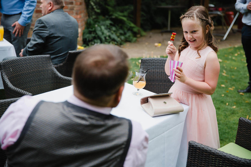 flower girl showing off sweets to her dad