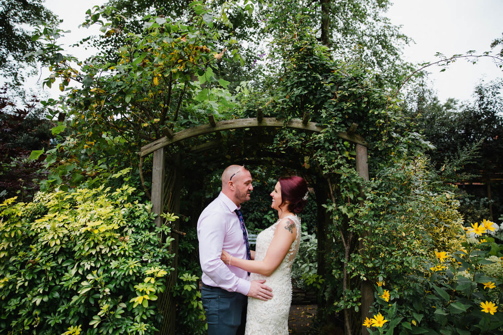 married couple holding each other underneath green flower garden archway