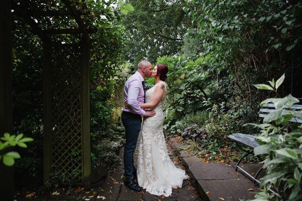 a moment together with the newly wedded couple. Couple kissing on pathway surrounded by green trees and bushes